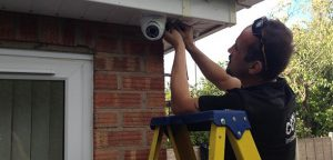 CCTV installer fitting a camera to a house